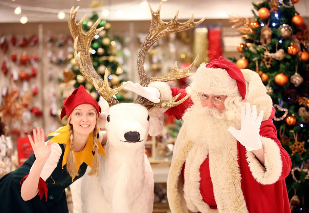 Santa Claus poses for a photograph with an Elf in the Christmas Shop, at Selfridges department store, on Oxford street, London